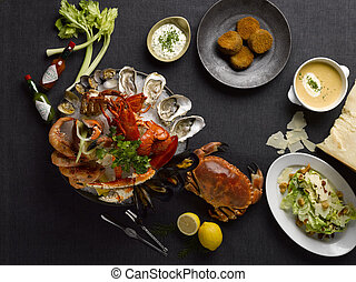 The deli mezza seafood meal with crab, lobsters, shrimp, oyster, clams, mussel, lemon, lettuce and soup on the table