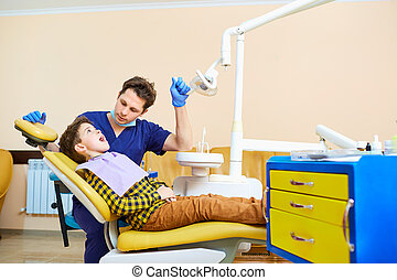 The dentist checking the teeth of  boy teenager.