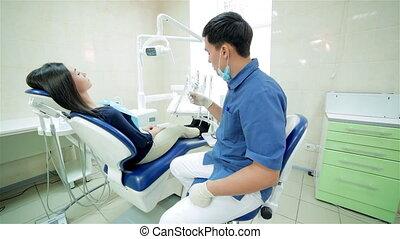 The dentist closer to patient sitting in the dental chair...
