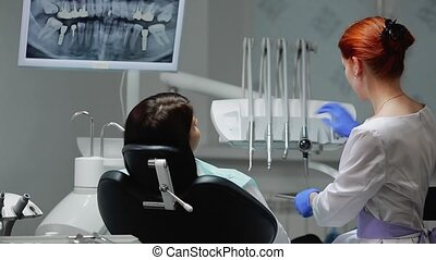 The dentist completes his work with a patient. Removes Bor...