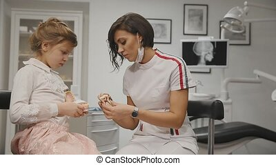 The dentist conducts a consultation a little girl showing how to brush teeth with a toothbrush using a denture. Close-up. Girl learns to brush teeth with braces.