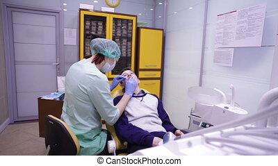 The dentist examines the teeth teen boy