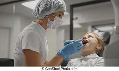 The dentist inspects the braces a little girl and checks the...
