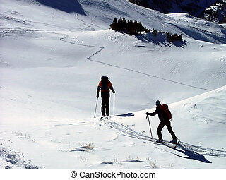 The Descent - two back country skiers beginning their...