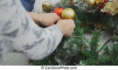 The designer fastens the gold ball to the Cristmas wreath by...
