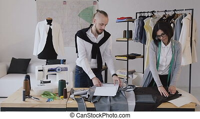 The designer of clothes and dressmaker develops a new collection of clothes at the modern small atelier. Successful completion of the working day. Fashion designers are focused on their work