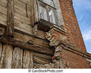 The destruction of the facade of an old wooden house
