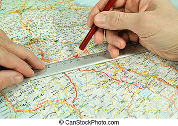 One can see the hands of man determinating a course by the red pencil and rule on the touristic map