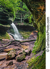 A seasonal waterfall flows over a rocky cliff into the Devil's Punchbowl at the head of a canyon in Indiana's scenic Shades State Park.