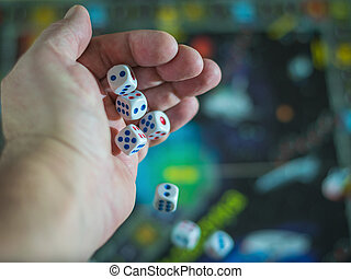 The dice fall from his hand on a colorful game Board.