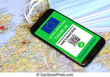 The digital green pass of the European Union with the QR code on the screen of a smartphone. Covid or Coronavirus vaccine certificate, with mask and map of Europe