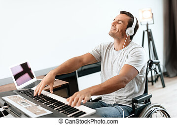 The disabled person is sitting in a wheelchair in front of the synthesizer. He plays music.