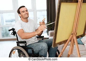 The disabled person is sitting in a wheelchair opposite the easel. He draws a picture.