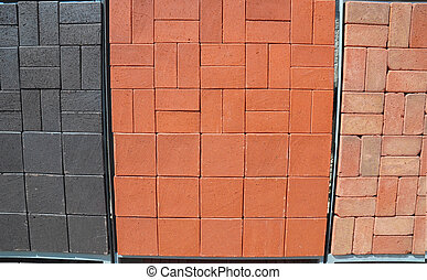 The display of black, red and orange patio pavers, paving stone with a single basketweave pattern for sale.