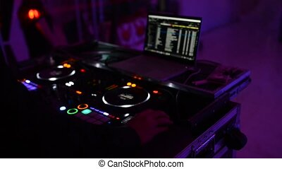 The DJ at the disco is working behind the remote control....