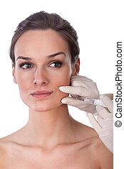 The doctor does injection to the face of woman