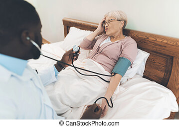 The doctor examines an elderly patient in a nursing home.