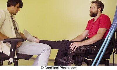 The doctor examines the patient's leg and talking with him