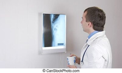 The doctor examines the X-ray and drinks a hot drink. White wall and Nigatoscope with ribs and thorax