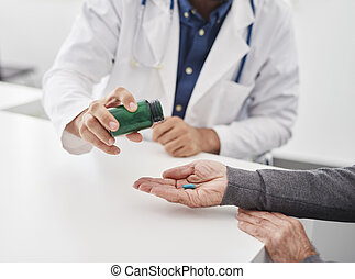 The doctor gives medicine to the patient.