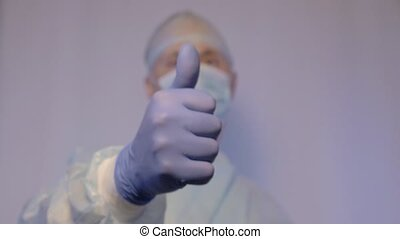 The doctor is a surgeon in a medical mask, shows the patient that everything is fine He lifts his thumb up and is positively tuned