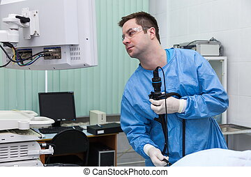 The doctor makes examination at the endoscopy department.