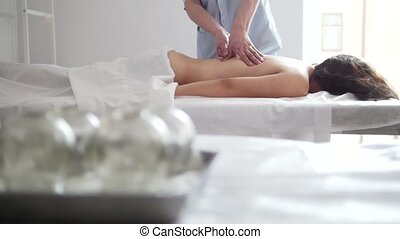 The doctor massages the woman's back on the table in the...