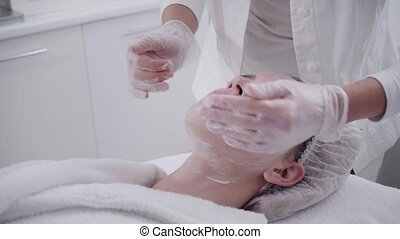 The doctor removes the gel from the patients face and apply...