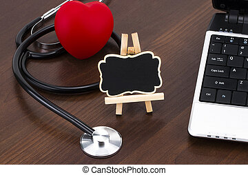 the doctor's desk with laptop, stethoscope and red heart and blackboard with empty space for a text