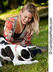 The dog en his owner - Blond girl and a american bulldog in...