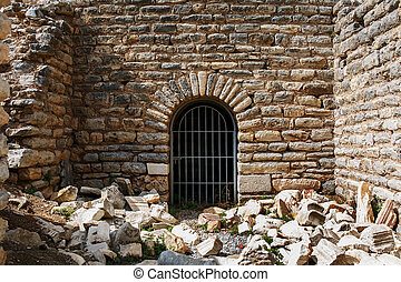 The door is from the metal grille of an ancient antique building, a castle of stone with sprawling blocks.
