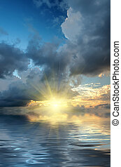 The dramatic sky and sun rays at sunset on the sea background