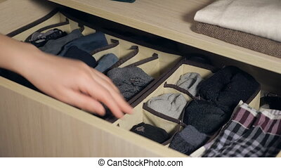 The drawer with underwear in the closet. Girl organizing...