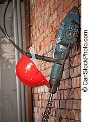 The drill and the red helmet of the Builder weigh on a brick wall