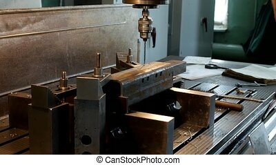 The drilling machine drills an opening in a metal workpiece,...