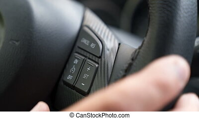 The driver's hand presses the car's on-board computer...