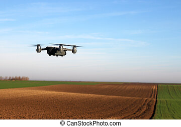 The drone is flying over the field landscape