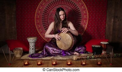 The drummer in action - Young woman playing drum, ethnic...