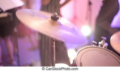 The drummer plays the cymbals at a concert. The drummer hits the plate drum.