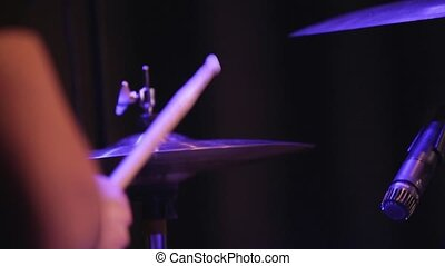 The drummer plays the drum at the concert.