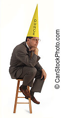 the dunce - executive thinking on a stool, wearing a dunce...
