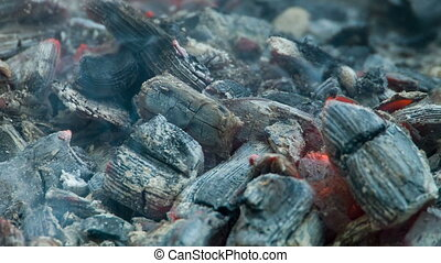 The dying coals embers in the brazier smoke and burn -...