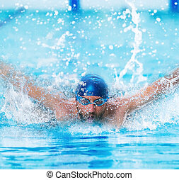 dynamic and fit swimmer in cap breathing performing the butterfly stroke