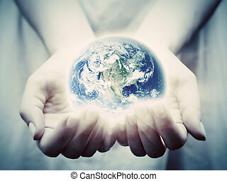 The earth shines in young woman hands. Save the world