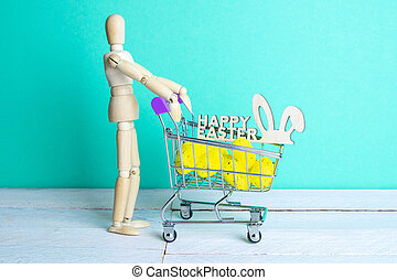 The Easter concept. Figure of a wooden man with a basket filled with eggs. In the background is a wooden rabbit and a sign of a Happy Easter