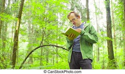 The ecologist in a forest examining plant - A scientist...