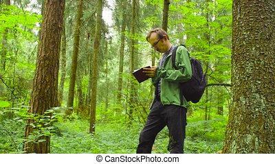 The ecologist in a forest writing in notebook. - The...
