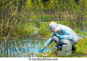 The ecologist takes a sample of water from a forest reservoir in protective clothing