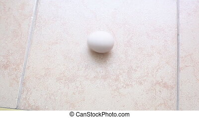 egg spins - the egg spins on the tile. Video close-up, high...