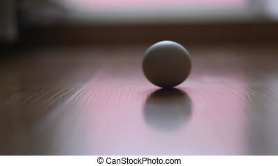 the egg spins on the tile. Video close-up, high quality